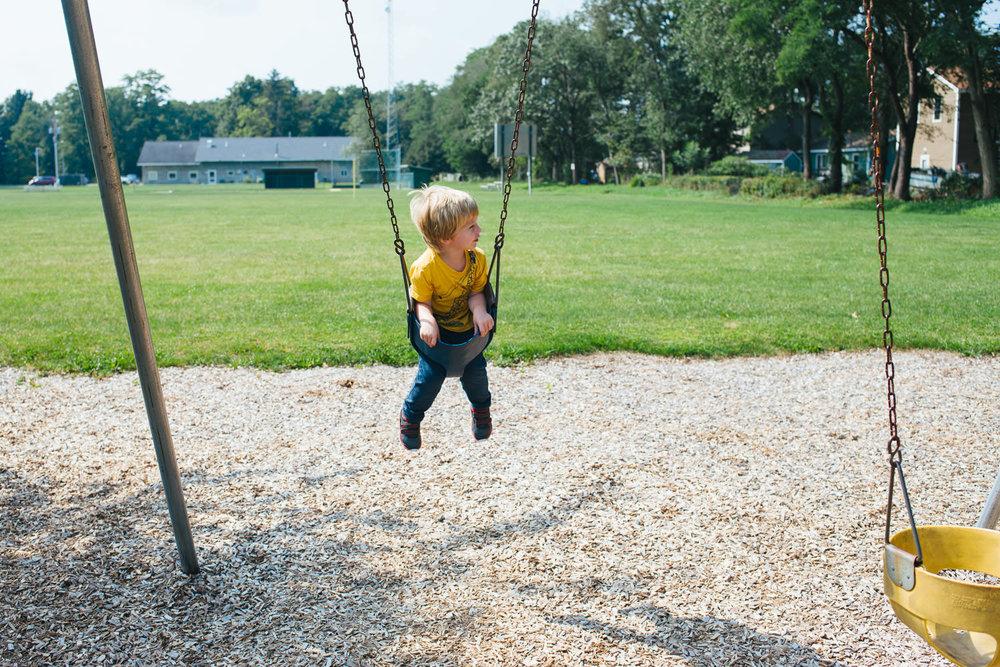 A little boy swings on the swing.