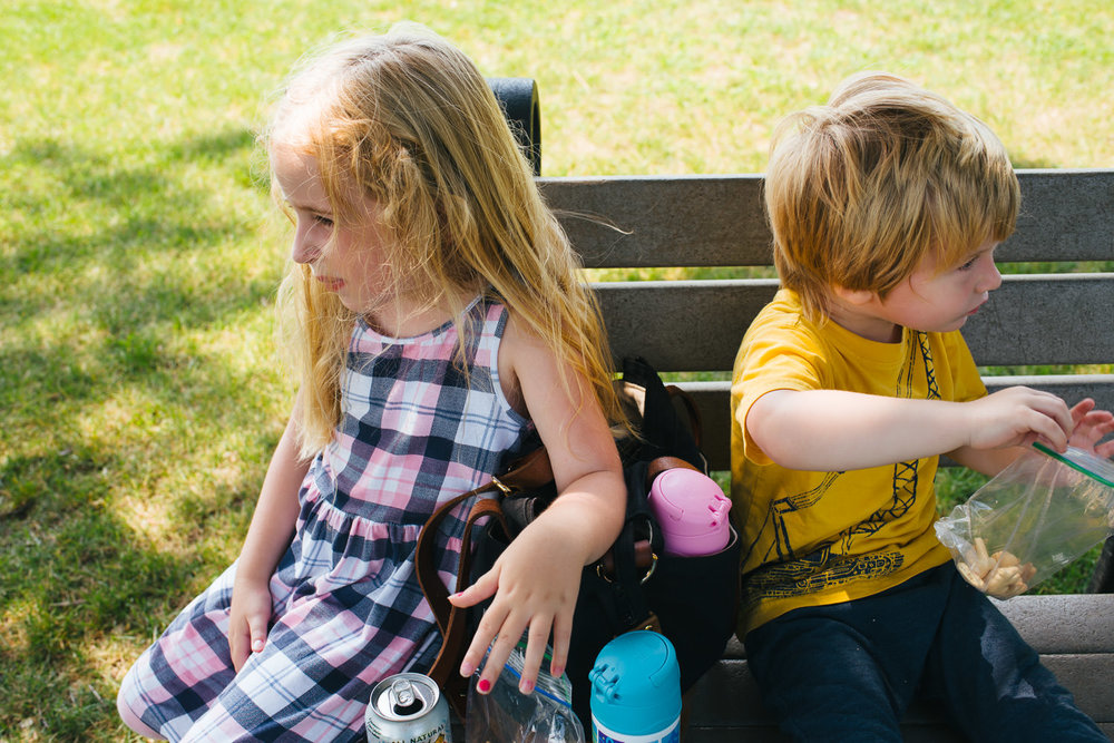 Two kids sit on a bench at the park.