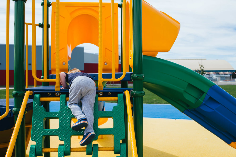A little boy plays on a vibrant colored playground.