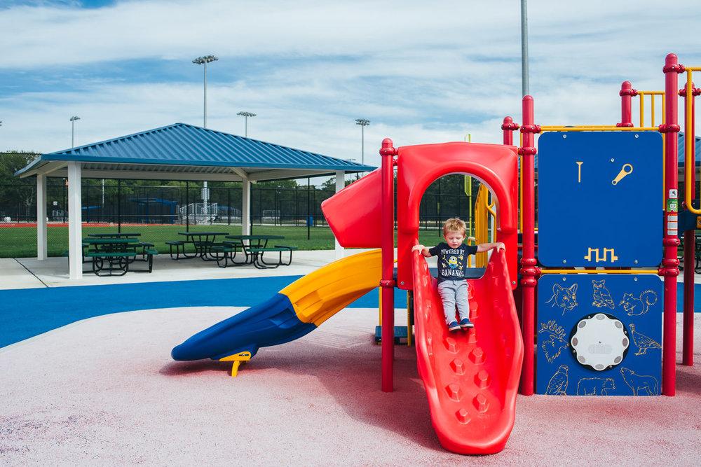 A little boy slides down a red slide at Eisenhower Park.