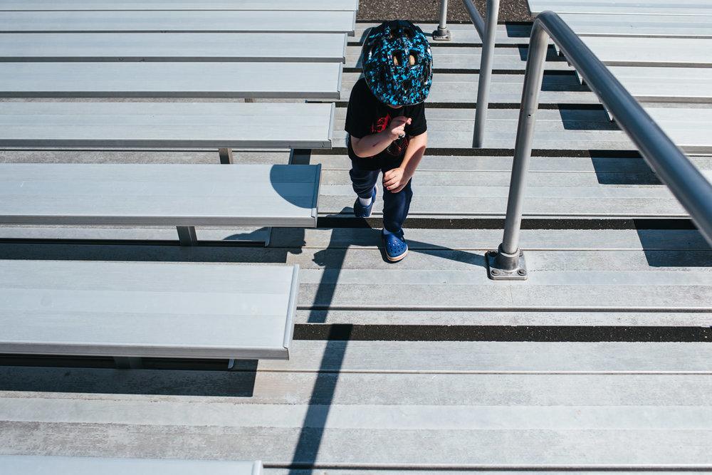 A little boy climbs steps of bleachers.
