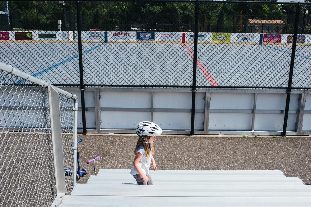 A little girl runs across the bleachers.