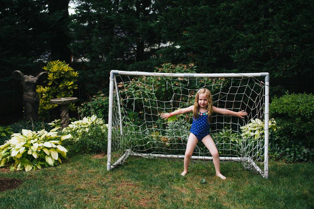 A little girl plays goalie.
