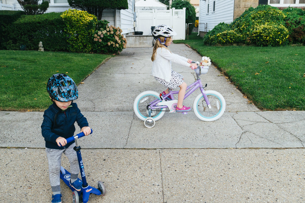 Two kids ride bikes and scooters down the sidewalk.