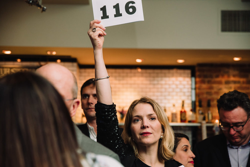 A woman bids for an item at a charity auction.