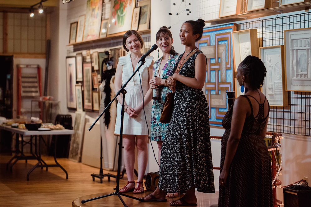 Three women speak at a microphone at the Project Life Center in Queens.
