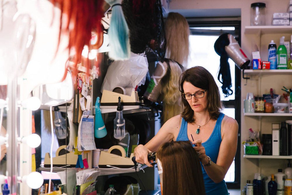 A woman styles wigs in a Broadway dressing room.