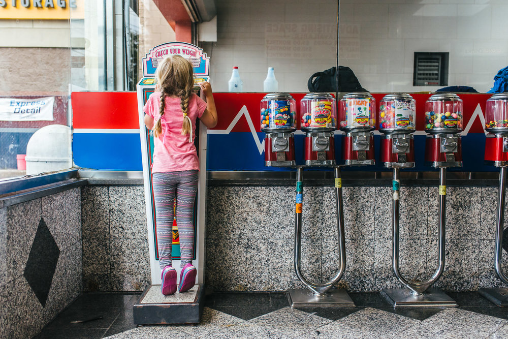 A little girl stands on a coin operated scale at the car wash.