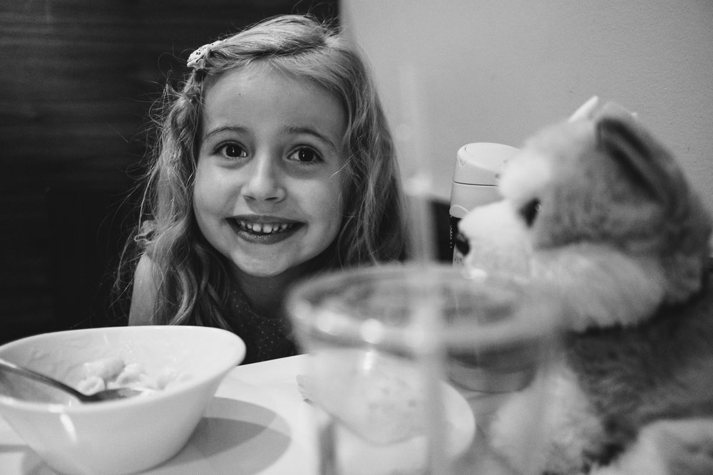 A little girl smiles at a table at Panera.