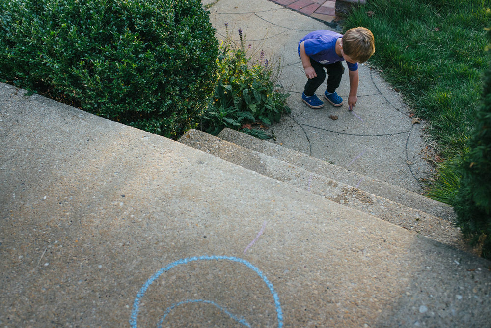 A little boy drawing a chalk circle.