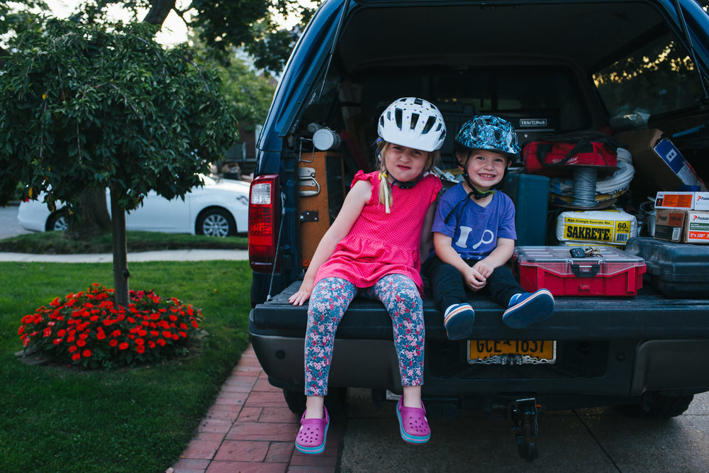 Siblings sit in the back of their father's truck.