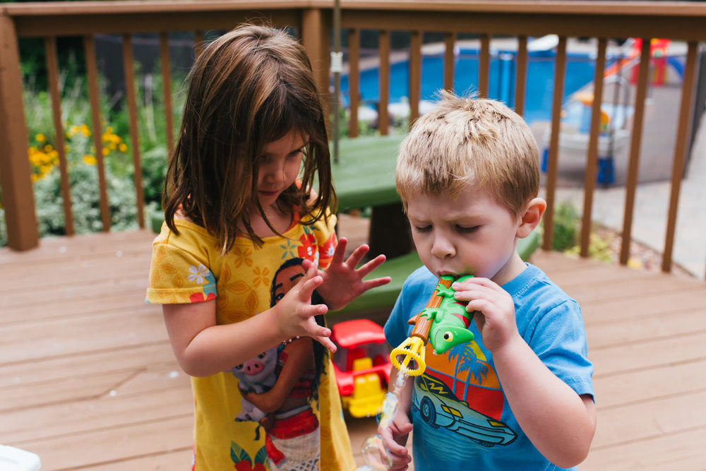 A girl and a boy blow bubbles in a backyard.