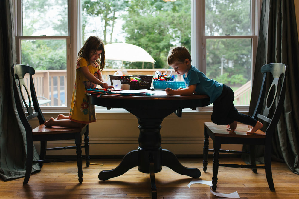 A boy and a girl draw at a table.