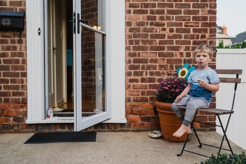 A little boy sits on a chair on his front stoop.