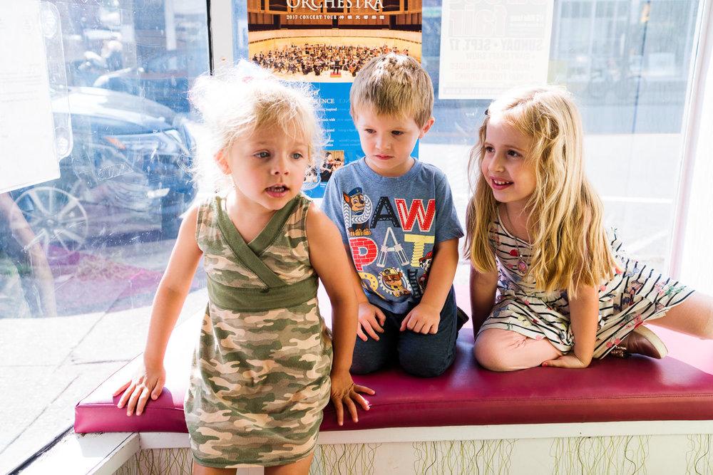 Three children sit in a window seat at a frozen yogurt shop.