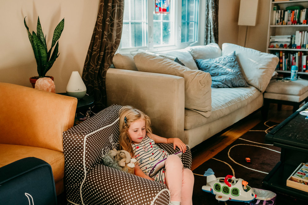 A little girl relaxes in her living room.