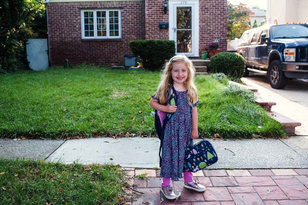 A little girl heads off to school with her backpack and lunch box.