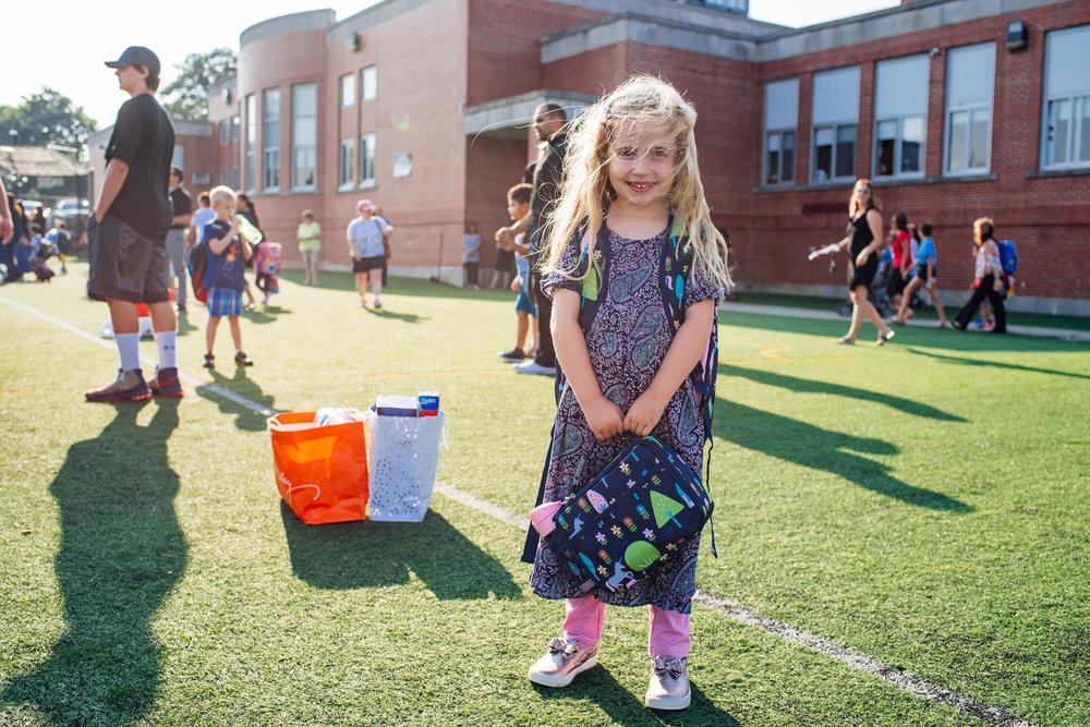 A little girl smiles outside her school.