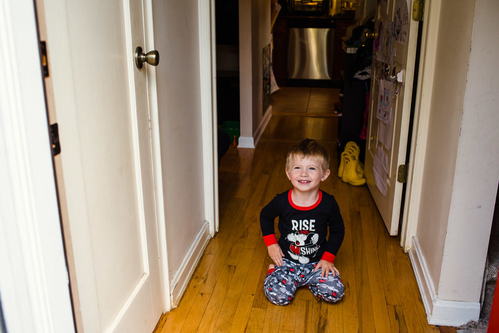 A little boy crouches in a hallway in his pajamas.