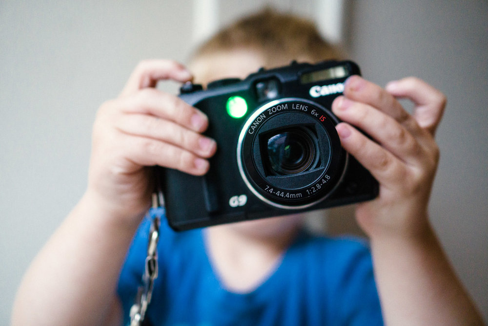 A little boy takes a picture with an old Canon G-9.