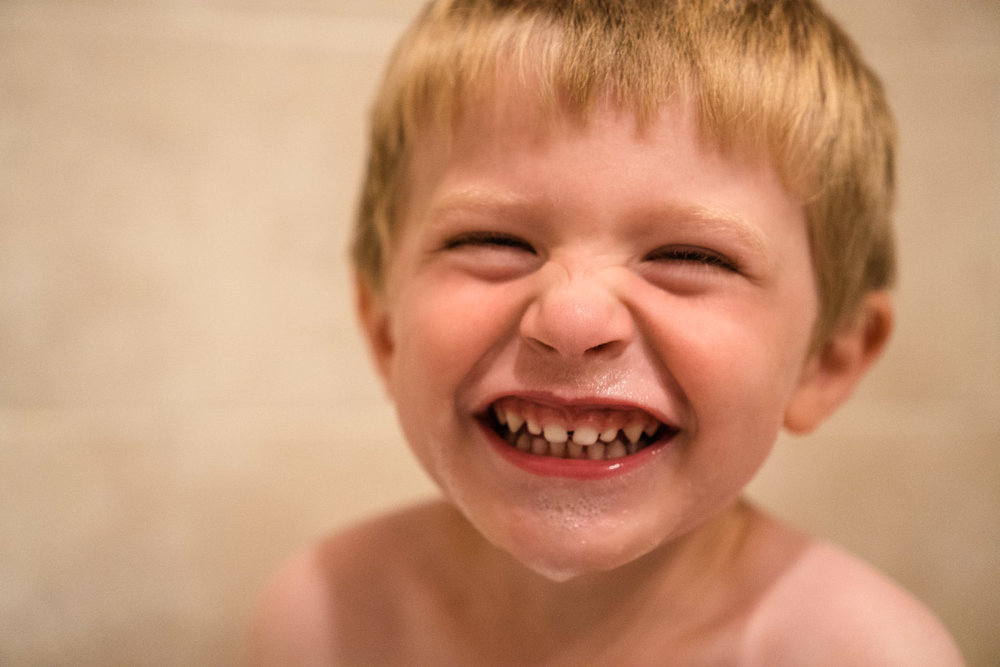 A little boy laughs in the bath.