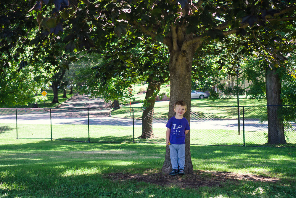 A little boy smiles underneath a tree.
