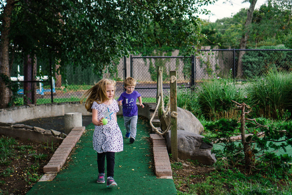 Kids run through a mini golf course.