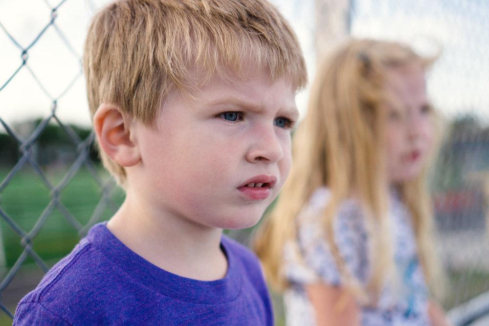 A little boy watches hockey from bleacher seats.