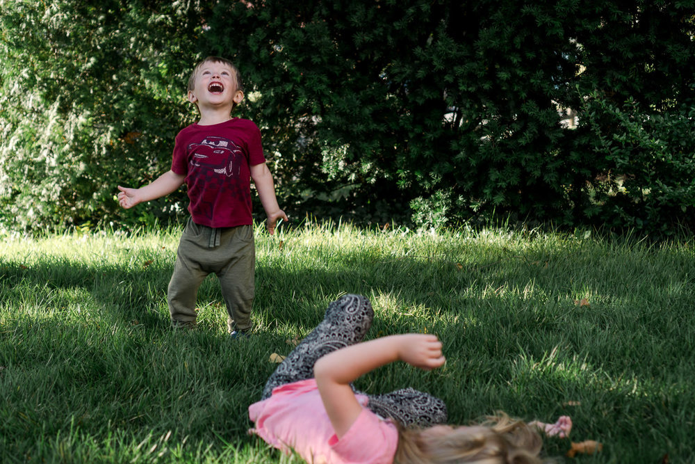 A brother and sister play on their front lawn.