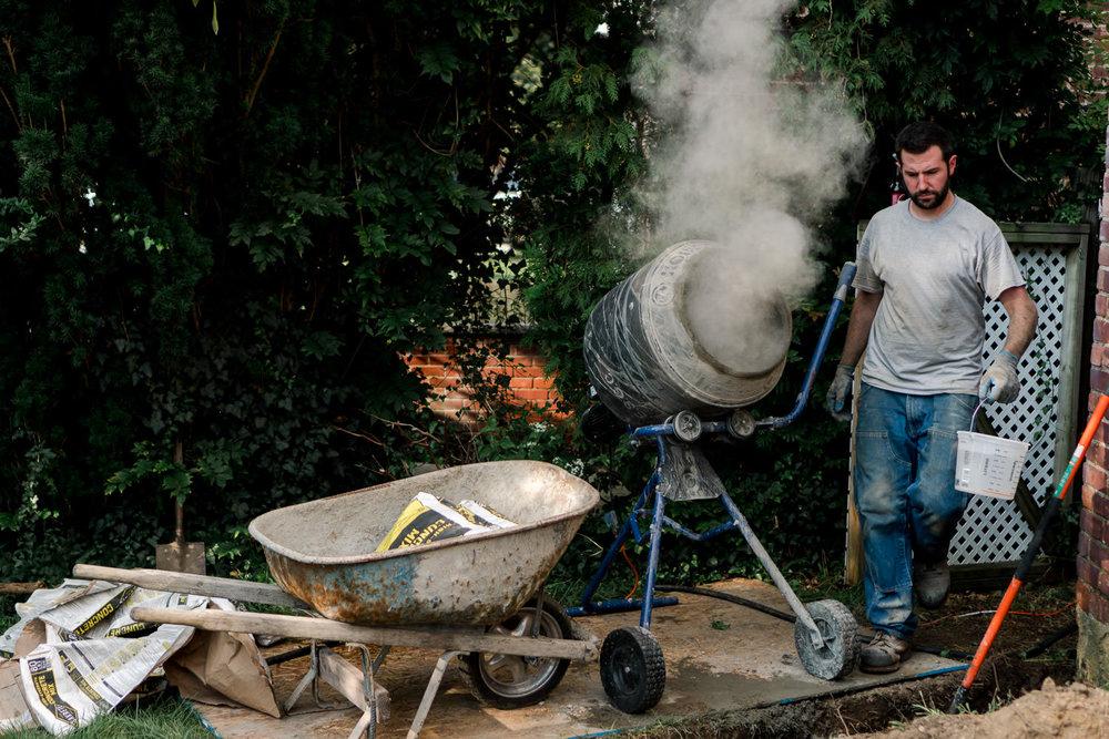 A man mixes cement.