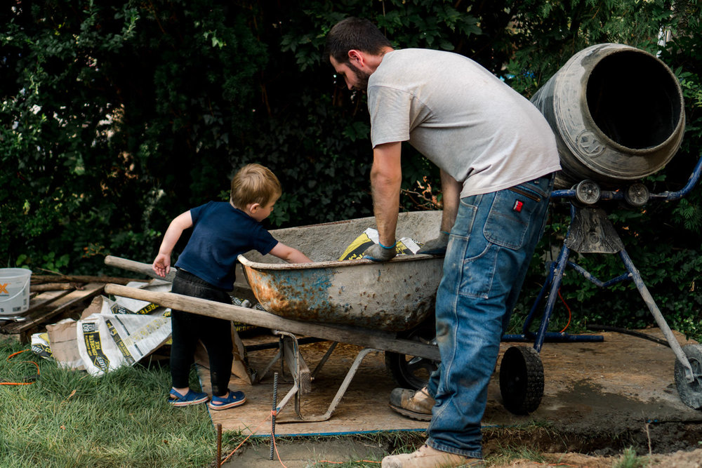 A little boy helps his dad mix cement.