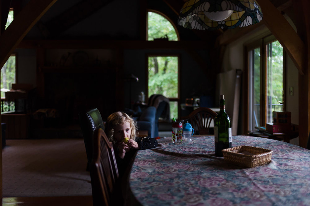 A little girl sits in dim light at the dining room table.