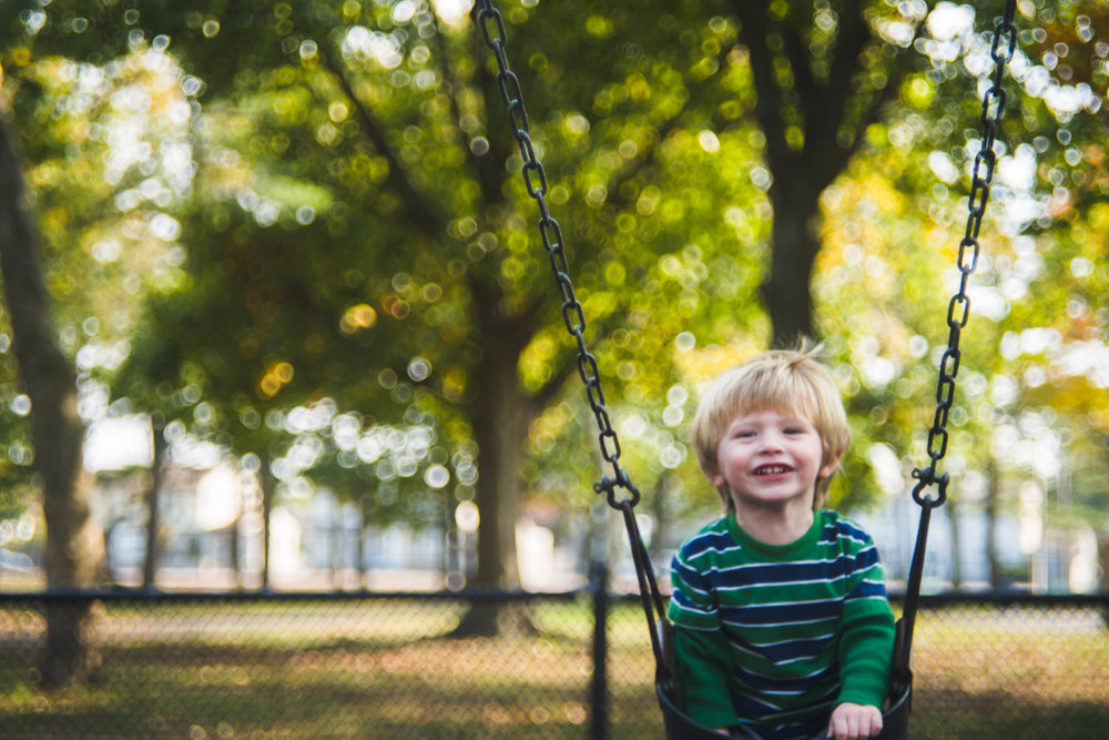 A little boy swings on a swing with fall trees behind him.