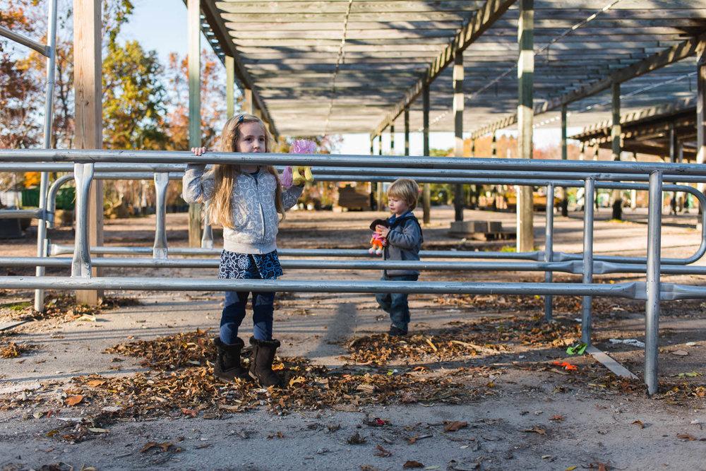 Two little kids climb a shopping cart corral at Hicks Nursery.