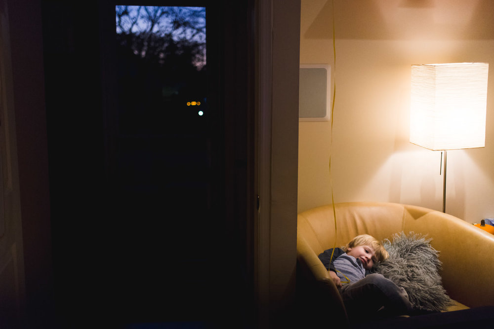 A little boy rests in an armchair in the dim light of the living room.