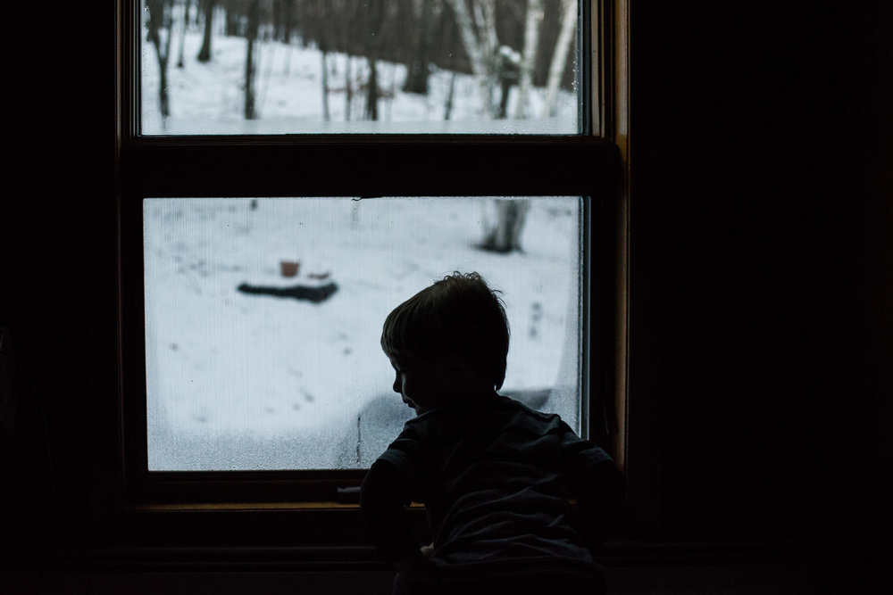 A little boy looks out a window at snowy surroundings.