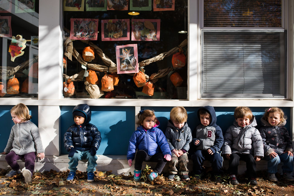 Children sit outside their classroom bundled in jackets.