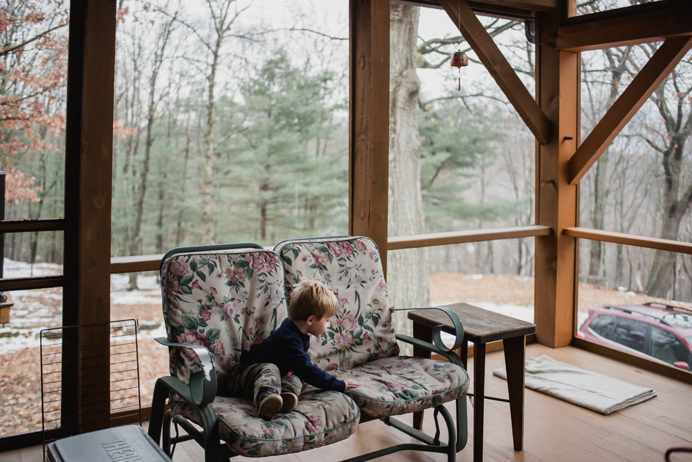 A little boy sits on an enclosed porch in the fall.