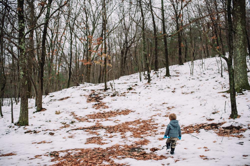 A little boy walks through snowy woods.