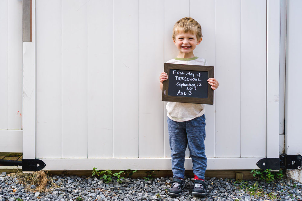 A little boy poses for his first day of preschool.