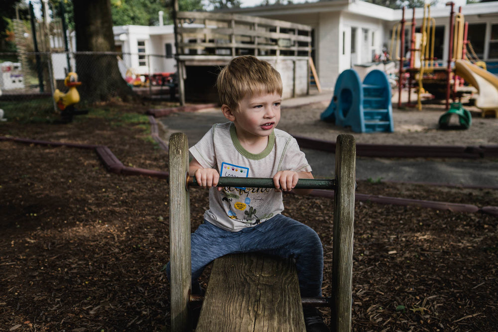 A little boy sits on a seesaw at his preschool.