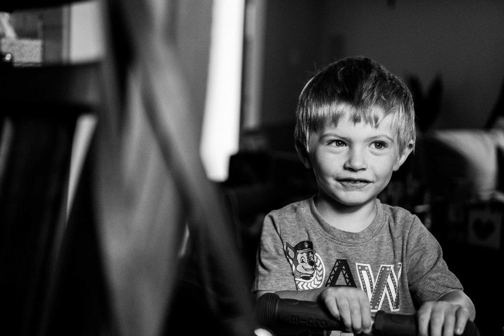 A little boy smiles bashfully.