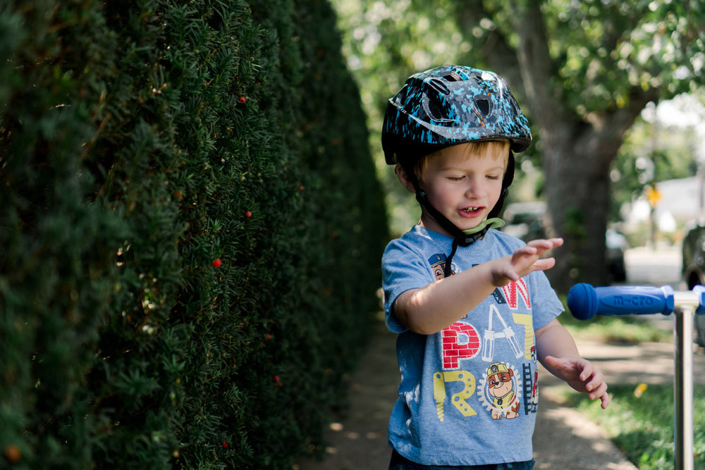 A little boy wears a helmet riding his scooter.