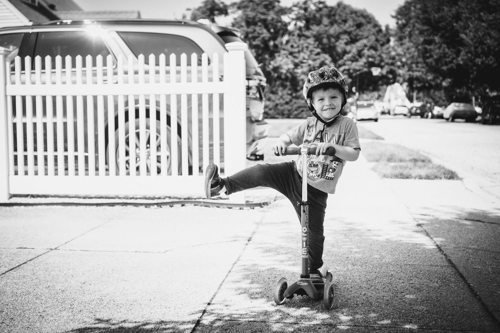 A little boy extends his leg at a right angle while riding his scooter.