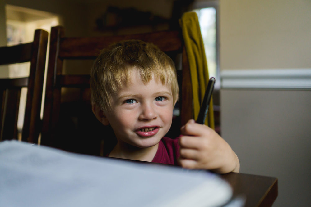 A little boy smiles as he sits in his chair at the dining room table.