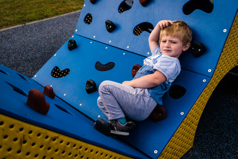 A little boy rests on a small climbing wall at the playground.