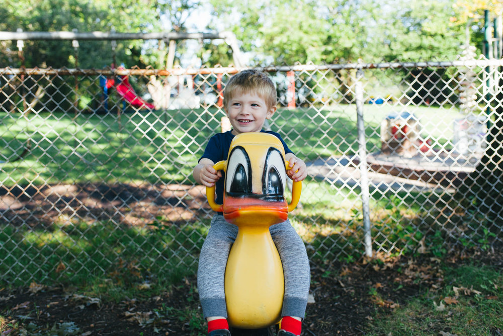 A little boy plays on a ride-on duck at nursery school.