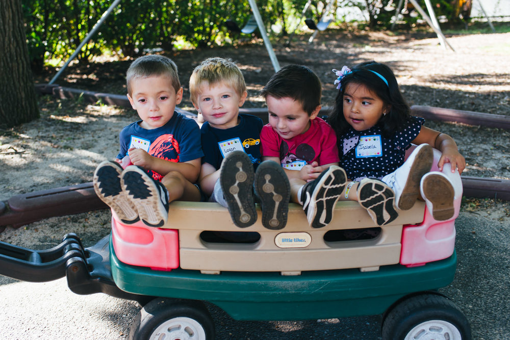 Preschoolers ride in a wagon on the playground.
