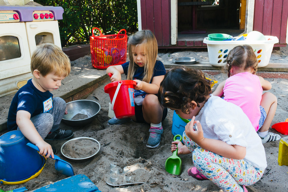 Preschoolers play in the sandbox at school.
