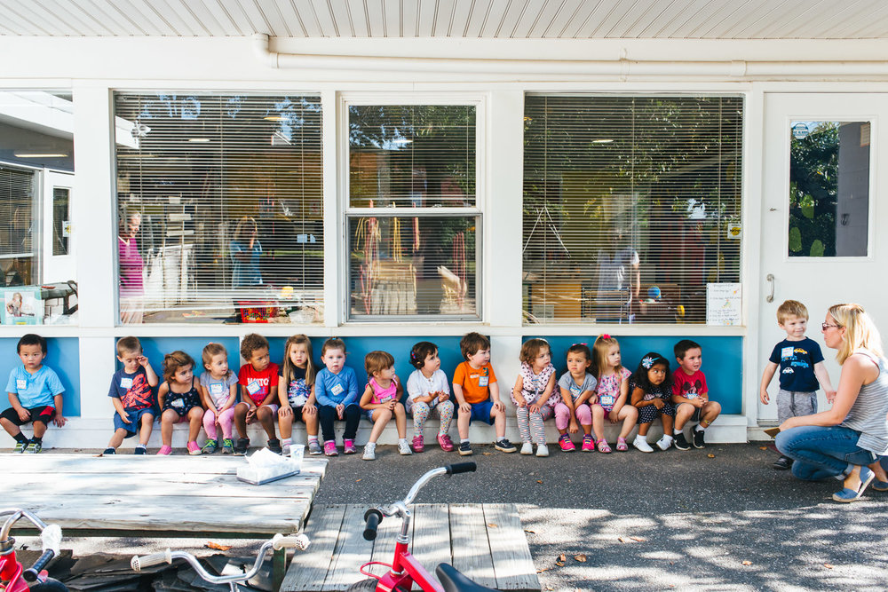Preschoolers line up outside their classroom after recess.